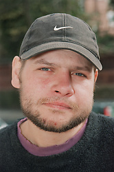 Portrait of male resident of Young Persons' Resettlement hostel wearing baseball cap,
