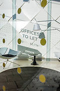 The shadows of a sign for Offices to Let is seen on a white wall in a corporate foyer in the City of London.