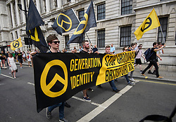 © Licensed to London News Pictures. 14/07/2018. London, UK. Members of the group Generation Identity join Supporters of U. S President Donald Trump and Tommy Robinson at a rally on Whitehall, central London. Trump is on his third day of a 4 day visit to the UK, which so far has seen him hold talks with British PM Theresa May and meet HRH Queen Elizabeth II. Photo credit: Ben Cawthra/LNP