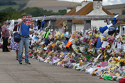 © Licensed to London News Pictures. 02/09/2015. Shoreham, UK. A man takes a photograph of floral tributes placed on a bridge near the site of the crashed Hawker Hunter fighter jet. The aircraft crashed while performing at the Shoreham air show on August 22, 2015 killing 11 people on the ground. As an inquest into the deaths opened today in nearby Horsham, the name of the last of the victims Graham Mallinson was released.  Photo credit: Peter Macdiarmid/LNP