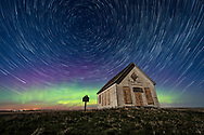 The 1910 Liberty Schoolhouse, a classic pioneer one-room school, on the Alberta prairie under the stars on a spring night, with circumpolar star trails circling Polaris, and an aurora dancing to the north. Moonlight from the 8-day-old waxing Moon provides the illumination. <br /> <br /> This is a stack of 155 exposures for the sky for the star trails, and a mean-combined stack of 8 exposures for the ground to smooth noise, with a vintage effect using Luminar applied to the ground for the rustic tone. Star trail stacking with Advanced Stacker Plus Actions in Photoshop with Ultrastreaks effect. <br /> <br /> With the Laowa 15mm lens and Sony a7III camera. All 20 seconds at f/2.8 and at ISO 800, and taken as part of a 360-frame time-lapse.