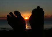 Feet silhouettes at sunrise or sunset, relaxing at the beach.