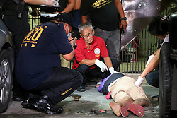 "September 30, 2016 - Philippines - (EDITORS NOTE: Image depicts death.) Members of S.O.C.O. (Scene of the Crime Operatives) process the crime scene and the remain of unidentified suspect after was pin down by the members of Philippine National Police (PNP) after the gun battle in Sta. Cruz Manila City. S.O.C.O. team members found a small sachet of methamphetamine ""shabu"" on the pocket of suspect. (Credit Image: © Gregorio B. Dantes Jr/Pacific Press via ZUMA Wire)"