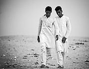 Junge Männer bei der Rückkehr von ihrem  Ausflug nahe des Ufers des Ganges. Was auch immer an dieser Oede intressant ist.