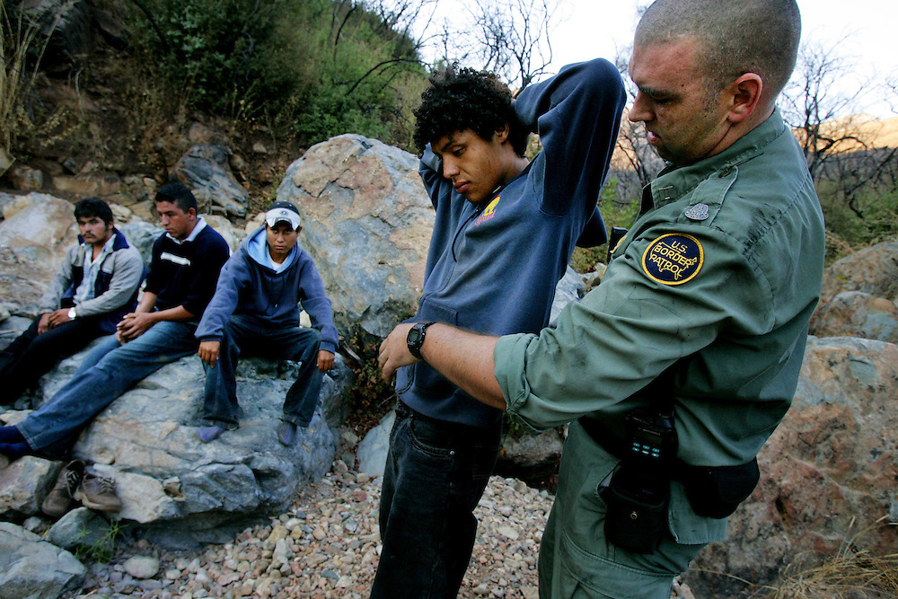 ADVANCE FOR STORY BY ELLIOT SPAGAT SAN DIEGO BUREAU:Border Patrol agent Mark Cary secures plastic handcuff on a group of illegal immigrants caught in the Otay Mesa Mountain Range, just East of San Diego, on Wednesday, October 12, 2005.  Cary is part of an elite Border Patrol unit that combs remote parts of the border that are unaccessable to vehicles.(AP Photo/Sandy Huffaker)