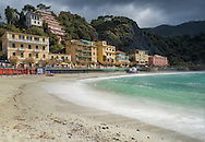 Beach at Monterosso al Mare, Cinque Terre.<br /> <br /> Monterosso al Mare is located at the center of a small natural gulf, protected by a small artificial reef, to the east of Punta Mesco in the Riviera of La Spezia. It is the westernmost of the Cinque Terre. In the west part of the original village, beyond the hill of the Capuchins, it is the village of Fegina, natural expansion and characterized by a relatively modern tourist resort facility compared to the ancient village that is reachable through a tunnel of a few tens of meters. The local train station is located at Fegina and the beaches are relatively larger compared to the narrow cliffs that characterize the other villages of the Cinque Terre.
