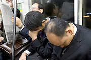 business commuters napping on a train Tokyo Japan