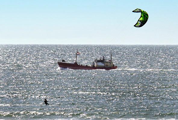 Nederland, Scheveningen, 20-6-2018Een vissersschip vaart richting haven . Op de voorgrond een windsurfer .Foto: Flip Franssen