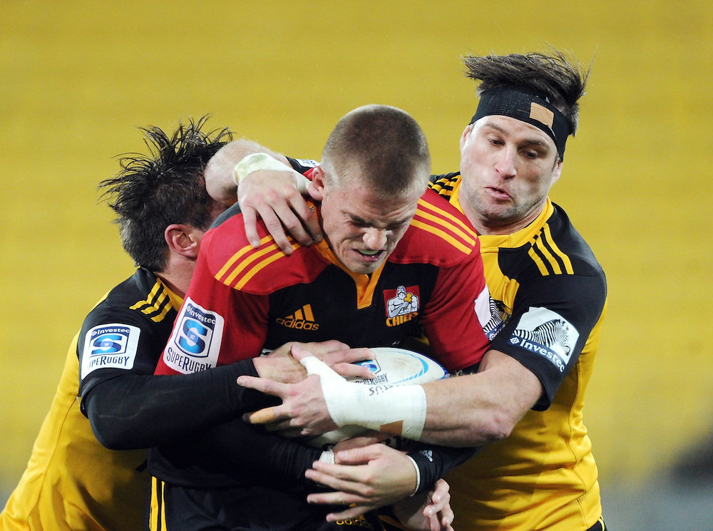 Chiefs' Gareth Anscombe, centre, wrapped up by Hurricanes' Cory Jane in the Super Rugby match at Westpac Stadium, Wellington, New Zealand, Saturday, May 24, 2014. Credit:SNPA / Ross Setford