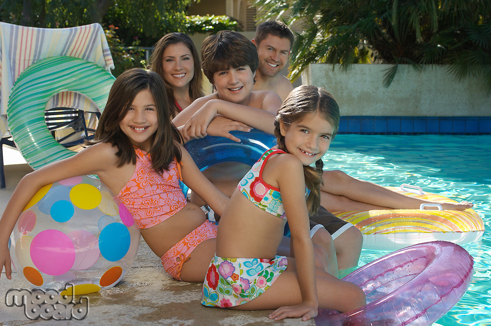 Family with two girls and boy with inflatable rafts sitting by swimming pool, portrait