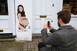 © Licensed to London News Pictures. 13/11/2014. LONDON, UK. A man takes pictures of a spray-painted picture of the pregnant Duchess of Cambridge, naked with a miniature crown balancing on her belly, made by graffiti artist Pegasus on a wall in Islington, north London. Photo credit : Tolga Akmen/LNP