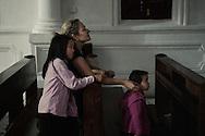 Carmen avec ses deux enfants adoptes  Gemma (2 ans et demi) et  Carole (7 ans) prient dans l'eglise catholique francaise de Shamian.