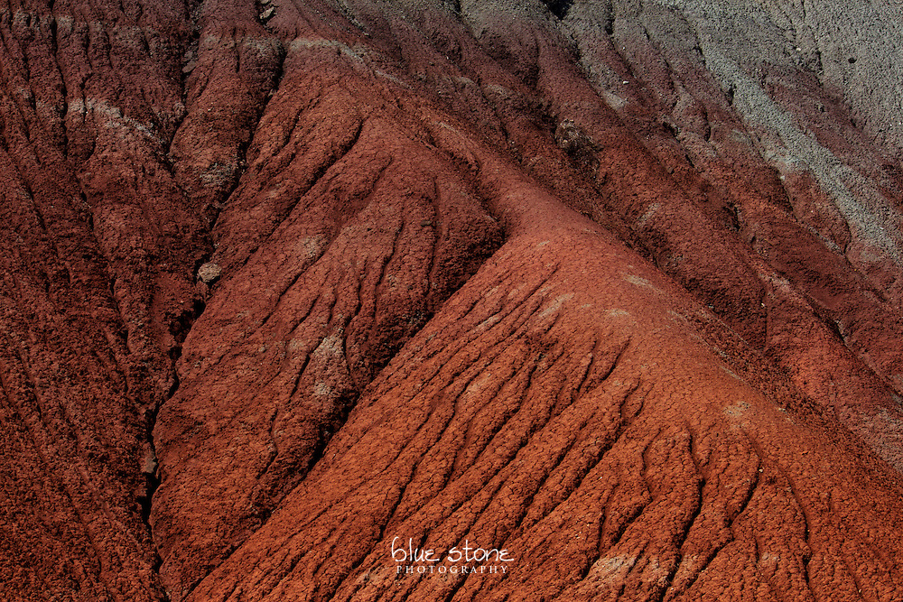 A natural erosion pattern in dark red, rust and slate grey rock.<br />