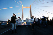 Dawn Garcia, of Richland, left, and Aaliyah Maldonado, 11, of Kennewick, carry a sign over the cable bridge Saturday during a protest stemming from the officer involved shooting death of Antonio Zambrano-Montes.