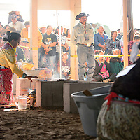 090314  Adron Gardner<br /> <br /> Koltey Tso, left, stokes a fire during the Miss Navajo fry bread competition at the Navajo Nation Fairgrounds in Window Rock Wednesday.