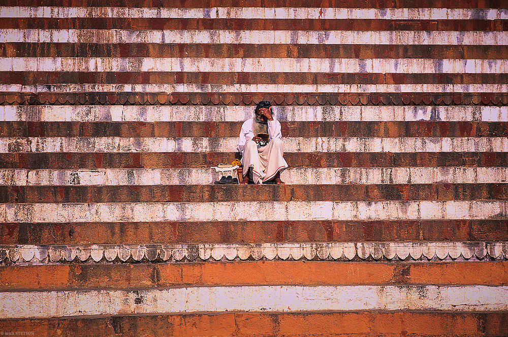 — At sunrise, a  holy man reads Hindu scripture in front of a temple along the sacred Ganges River.