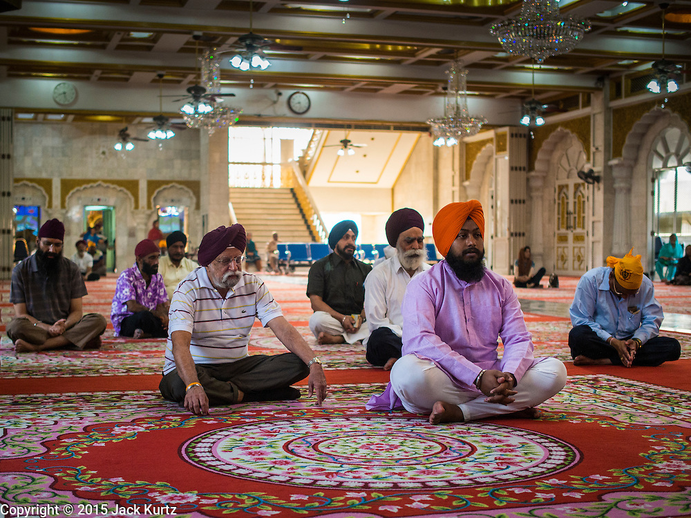 """08 FEBRUARY 2015  BANGKOK, THAILAND:  Sikh men in the Darbar Sahib (prayer hall) at Gurdwara Siri Guru Singh Sabha, the Sikh temple in Bangkok. Thailand has a small but influential Sikh community. Sikhs started coming to Thailand, then Siam, in the 1890s. There are now several thousand Thai-Indian Sikh families. Gurdwara Siri Guru Singh Sabha was established in 1913. Construction of the current building, adjacent to the original Gurdwara (""""Gateway to the Guru""""), started in 1979 and was finished in 1981. The Sikh community serves a daily free vegetarian meal at the Gurdwara that is available to people of any faith and background.   PHOTO BY JACK KURTZ"""