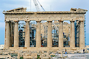 The Parthenon was first built from 447-438 BC, using Pentelic marble plus a wooden roof. Scaffolding and crane in 2001 support reconstruction for the 2004 Olympics, in Athens, Greece, Europe. The Parthenon is the largest Doric-column temple ever completed in Greece. It was designed as a treasury for tribute money moved from Delos Island and was dedicated to the worship of Athena. A huge, 12-meter tall statue of Athina Polias was placed in 432 BC. The treasury stored money from the Delian League, which later became the Athenian Empire. In the 400s AD, the Parthenon was converted into a Christian church dedicated to the Virgin Mary. After the Ottoman conquest, it was turned into a mosque with added minaret in the early 1460s. In 1687, an Ottoman ammunition dump inside the building was ignited by Venetian bombardment. The resulting explosion severely damaged the Parthenon and its sculptures. In 1806, Thomas Bruce, 7th Earl of Elgin removed some of the surviving sculptures, with the Ottoman Turks' permission. These sculptures, now known as the Elgin Marbles or the Parthenon Marbles, were sold in 1816 to the British Museum in London, where they are now displayed. Greece wants them back. The Acropolis of Athens and its monuments were honored as a UNESCO World Heritage Site in 1987.