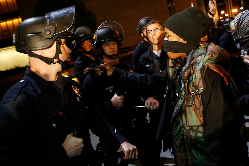 An LAPD officer is taunted by a protestor as police hold a skirmish line in front of the LAPD Headquarters as people protest the decision of the Ferguson grand jury and the death of Michael Brown on early morning Tuesday, November 25, 2014 in Los Angeles, Calif. (Patrick T. Fallon/ For the Los Angeles Times)
