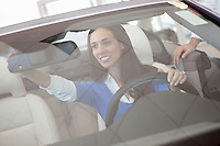 Woman adjusting rearview mirror of her new car