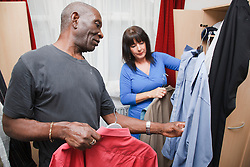 Elderly black man with white woman carer at home choosing shirts
