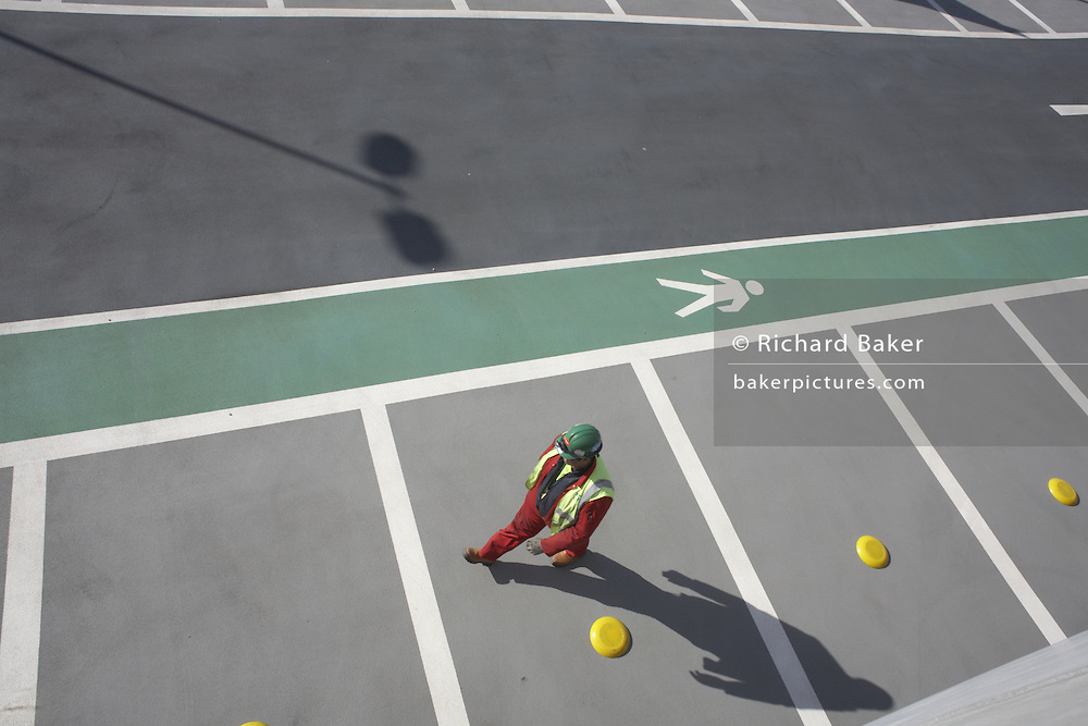 Construction worker walks along unused car parking bays outside newly-opened London Heathrow Airport's Terminal 5 building.