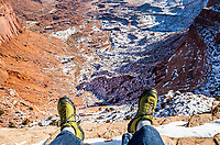A first person perspective of sitting on the edge of a cliff / dropoff looking down at feet hanging off the edge, Island in the Sky section of CanyonLands National Park, Utah, USA.