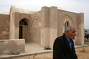 Palestinian Majid Asamna, stands outside the 3 room mud brick home he received from the United Nations  to replace his concrete one destroyed during the 22 day long Israeli offensive one year ago in the Ezbet Abed Rabbo district of the Jabaliya refugee camp in Gaza  December 17,2009. The multiple room mud homes can be built for around 10,000 dollars in one month, and are part of an initiative by the United Nations to work around the shortage of traditional  building materials that have been restricted by an ongoing Israeli and Egyptian blockade while continuing to provide Palestinian families with better alternative housing.