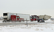 A car drives by a three semi truck accident in the median along Interstate 80 in Polk County in Iowa on Wednesday February 2, 2011.