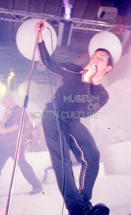 Tom Hingley singing into microphone, forward stage, Inspiral Carpets, Manchester, UK, circa 1990