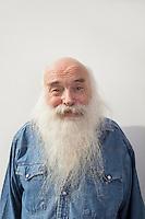 Portrait of senior man over gray background
