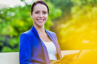 Portrait of Smiling young attractive businesswoman holding digital tablet while standing in park