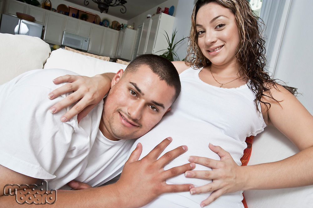 Portrait of expectant couple touching belly