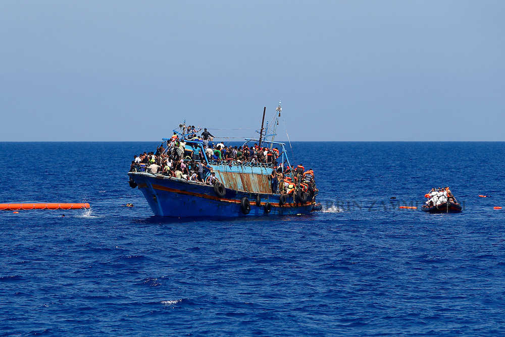 Migrants swim in the water after jumping off their overloaded wooden boat during during a rescue operation off the coast of Libya August 6, 2015.  An estimated 600 migrants on the boat were rescued by the international non-governmental organisations Medecins san Frontiere (MSF) and the Migrant Offshore Aid Station (MOAS) without loss of life on Thursday afternoon, a day after more than 200 migrants are feared to have drowned in the latest Mediterranean boat tragedy after rescuers saved over 370 people from a capsized boat thought to be carrying 600.<br /> REUTERS/Darrin Zammit Lupi <br /> MALTA OUT. NO COMMERCIAL OR EDITORIAL SALES IN MALTA