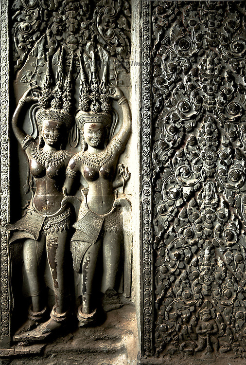 Angkor Wat, closeup of two Apsara dancers and panel of foliage ornament.  Apsaras in Khmer combination of Hindu and Buddhist traditions represent supernatural sacred nymphs.
