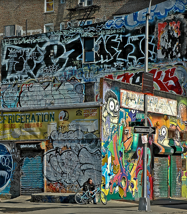 A cyclist waits by a wall full of graffitis at a corner of beford Avenue in Williamsburg, Brooklyn, 2008.