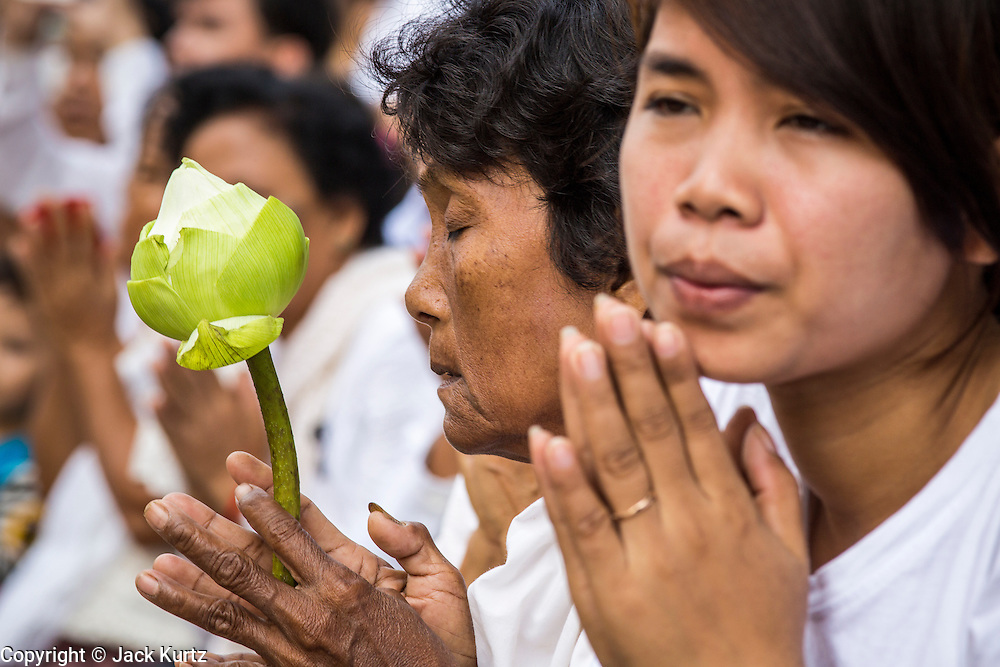 """01 FEBRUARY 2013 - PHNOM PENH, CAMBODIA:  Cambodian mourners watch the funeral procession of former King Norodom Sihanouk in Phnom Penh. Norodom Sihanouk (31 October 1922- 15 October 2012) was the King of Cambodia from 1941 to 1955 and again from 1993 to 2004. He was the effective ruler of Cambodia from 1953 to 1970. After his second abdication in 2004, he was given the honorific of """"The King-Father of Cambodia."""" Sihanouk died in Beijing, China, where he was receiving medical care, on Oct. 15, 2012. His cremation is will be on Feb. 4, 2013. Over a million people are expected to attend the service.   PHOTO BY JACK KURTZ"""