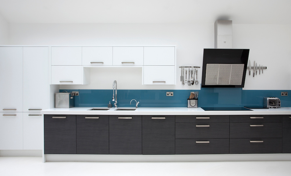 Long kitchen wall with units, cooker, hood and utensils