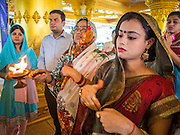 """09 SEPTEMBER 2013 - BANGKOK, THAILAND:  Indian women pray during Ganesha Chaturthi celebrations at Shiva Temple in Bangkok. Ganesha Chaturthi also known as Vinayaka Chaturthi, is the Hindu festival celebrated on the day of the re-birth of Lord Ganesha, the son of Shiva and Parvati. The festival, also known as Ganeshotsav (""""Festival of Ganesha"""") is observed in the Hindu calendar month of Bhaadrapada. The date usually falls between 19 August and 20 September. The festival lasts for 10 days, ending on Anant Chaturdashi. Ganesha is a widely worshipped Hindu deity and is revered by many Thai Buddhists. Ganesha is widely revered as the remover of obstacles, the patron of arts and sciences and the deva of intellect and wisdom.    PHOTO BY JACK KURTZ"""