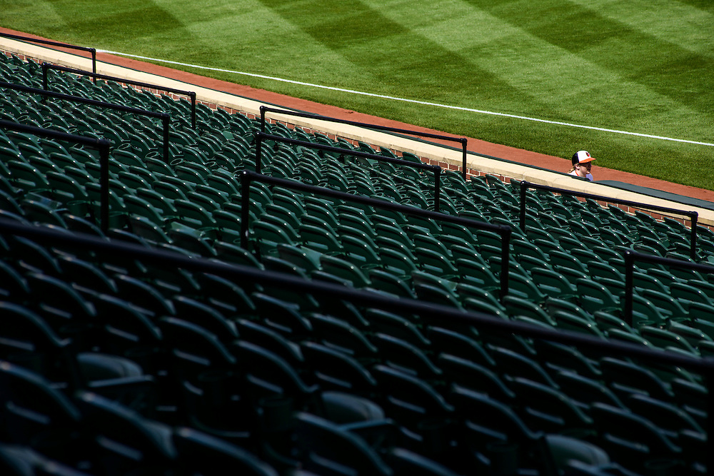 Baltimore, MD - April 29, 2015: Baltimore Oriole ball girl Emily Potere, 21, sits at an empty Oriole Park at Camden Yards on April 29, 2015. The civil unrest in Baltimore has forced the game between the Chicago White Sox and Baltimore Orioles to be closed to the public and moved to the afternoon. (Matt Roth for ESPN)