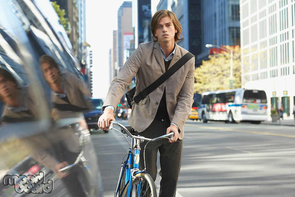 Man standing by bicycle on busy street portrait