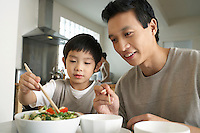 Young parent sitting at table watching son trying to use chopsticks
