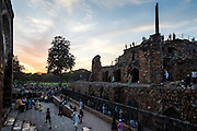 "19th March 2015, New Delhi, India. Dusk view of the three-tiered arcaded pavilion with an Ashokan Pillar atop it in the ruins of Feroz Shah Kotla in New Delhi, India on the 19th March 2015<br /> <br /> PHOTOGRAPH BY AND COPYRIGHT OF SIMON DE TREY-WHITE a photographer in delhi<br /> + 91 98103 99809. Email: simon@simondetreywhite.com<br /> <br /> People have been coming to Firoz Shah Kotla to leave written notes and offerings for Djinns in the hopes of getting wishes granted since the late 1970's. Jinn, jann or djinn are supernatural creatures in Islamic mythology as well as pre-Islamic Arabian mythology. They are mentioned frequently in the Quran  and other Islamic texts and inhabit an unseen world called Djinnestan. In Islamic theology jinn are said to be creatures with free will, made from smokeless fire by Allah as humans were made of clay, among other things. According to the Quran, jinn have free will, and Iblīs abused this freedom in front of Allah by refusing to bow to Adam when Allah ordered angels and jinn to do so. For disobeying Allah, Iblīs was expelled from Paradise and called ""Shayṭān"" (Satan).They are usually invisible to humans, but humans do appear clearly to jinn, as they can possess them. Like humans, jinn will also be judged on the Day of Judgment and will be sent to Paradise or Hell according to their deeds. Feroz Shah Tughlaq (r. 1351–88), the Sultan of Delhi, established the fortified city of Ferozabad in 1354, as the new capital of the Delhi Sultanate, and included in it the site of the present Feroz Shah Kotla. Kotla literally means fortress or citadel."
