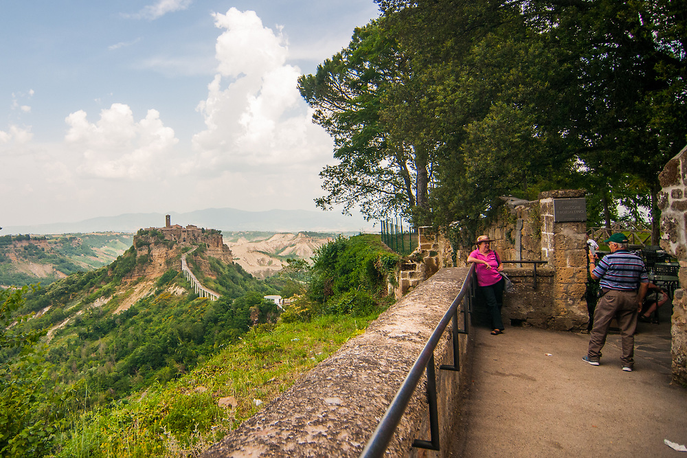 Tourists take a picture at the panoramic terrace at Civita di Bagnoregio.<br /> Civita di Bagnoregio is a town in the Province of Viterbo in central Italy, a suburb of the comune of Bagnoregio, 1 kilometre (0.6 mi) east from it. It is about 120 kilometres (75 mi) north of Rome. Civita was founded by Etruscans more than 2,500 years ago. Bagnoregio continues as a small but prosperous town, while Civita became known in Italian as La citt&agrave; che muore (&quot;The Dying Town&quot;). Civita has only recently been experiencing a tourist revival. The population today varies from about 7 people in winter to more than 100 in summer.The town was placed on the World Monuments Fund's 2006 Watch List of the 100 Most Endangered Sites, because of threats it faces from erosion and unregulated tourism.