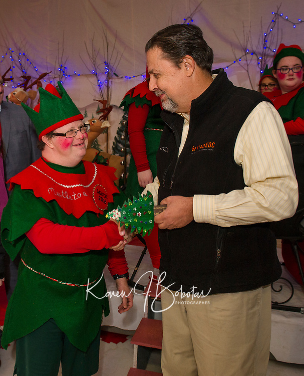 Mayor Ben Phillips receives the 2018 key to Christmas Village by Laconia Mayor Ed Engler as Christmas Village opens on Thursday evening.  (Karen Bobotas/for the Laconia Daily Sun)