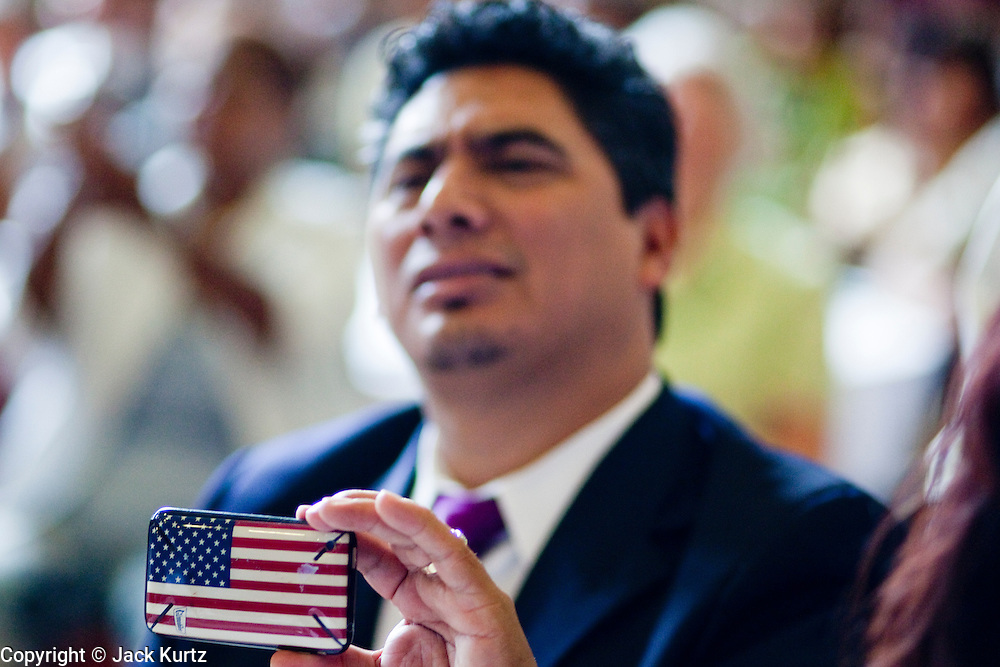 """19 JUNE 2009 -- PHOENIX, AZ: Rev. Asbel Gonzalez (CQ) uses a cell phone with an American flag to videotape Al Sharpton's speech Friday. The Rev. Asbel Gonzalez (CQ) uses a cell phone with an American flag to videotape Al Sharpton's speech Friday. Rev. Al Sharpton is in Phoenix Friday to protest the high profile """"crime suppression"""" sweeps conducted by the Sheriff's Department. Critics contend the sweeps use racial profiling to target Hispanics. PHOTO BY JACK KURTZ"""