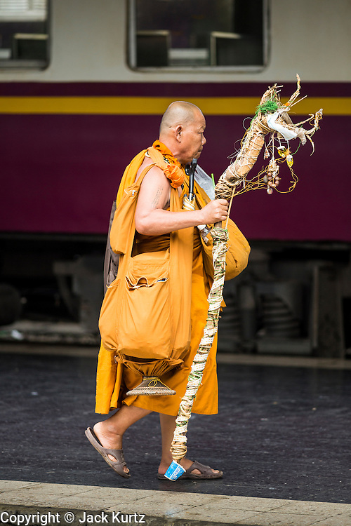 16 APRIL 2014 - BANGKOK, THAILAND: A Buddhist monk going back to his temple in a southern province walks to a southbound train in Hua Lamphong Railway Station in Bangkok. Thai highways, trains and buses were packed Wednesday as Thais started returning home after the long Songkran break. Songkran is normally three days long but this year many Thais had at least an extra day off because the holiday started on Sunday, so many Thais started traveling on Friday of last week.    PHOTO BY JACK KURTZ
