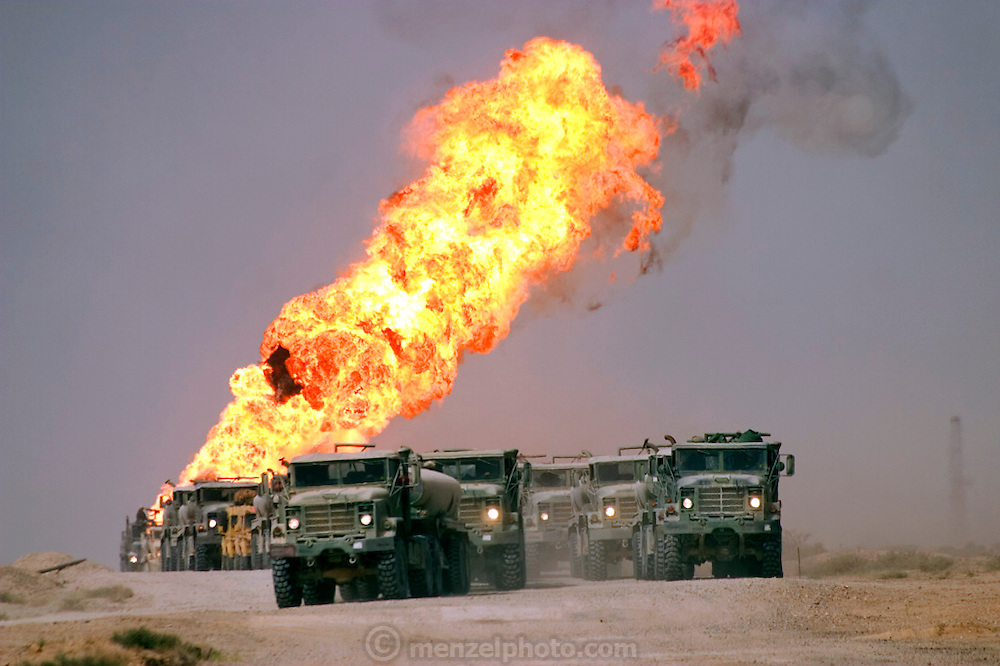 Heading north through the Rumaila Oil Field of Southern Iraq, convoys of fuel trucks carry the army's mechanical lifeblood past burning oil wells set ablaze by retreating Iraqi forces. The Rumaila field is one of Iraq's biggest oil fields with five billion barrels in reserve. The burning wells in the Rumaila Field were ignited by retreating Iraqi troops when the US and UK invasion began in March 2003. Rumaila is also spelled Rumeilah.