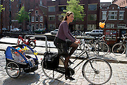 Een vrouw fietst op koninginnedag met twee kinderen in een fietskar door Groningen.<br /> <br /> At Queensday a woman is cycling with two children in a trailer in Groningen.