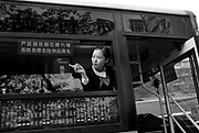 A uniformed bus attendant looks out of a window on a bus in Chongqing. Bus attendants collect fares from passengers.
